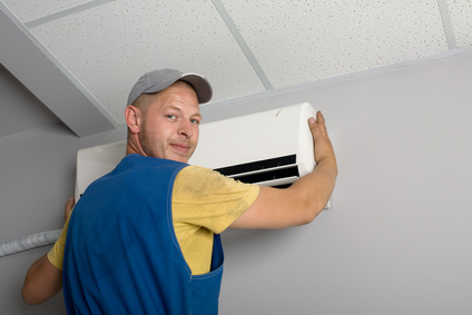 Young setup man installs the new air conditioner in office